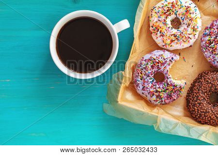 Delicious Glazed Donuts In Box And Cup Of Coffee On Turquoise Blue Surface. Flat Lay Minimalist Food