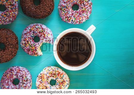 Delicious Glazed Donuts And Cup Of Coffee On Turquoise Blue Surface. Flat Lay Minimalist Food Art Ba