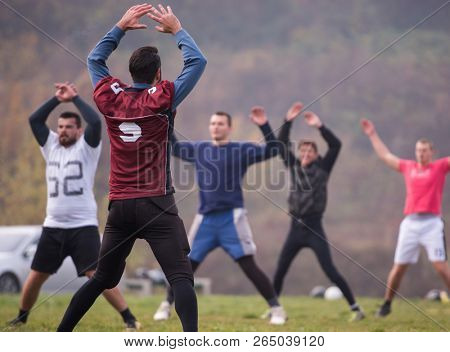 group of young american football players stretching and warming up together before a practice