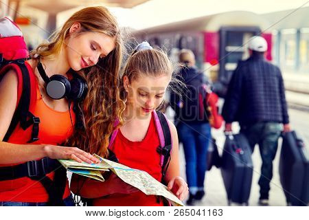 Traveller girl female wear headphones with backpack and tourism outfit paper map at railway station city outdoor. Terminal train locomotive and people with suitcase on background.
