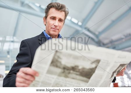 Businessman is reading a daily newspaper before a business trip in the airport or train station