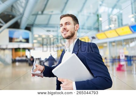 Young business man on business trip in airport terminal with laptop computer