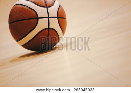 Basketball On Wooden Court Floor Close Up With Blurred Arena In Background. Orange Ball On A Hardwoo