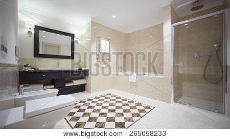Nice Bathroom In A Modern Style With Gray Tiled Walls. There Is A White Bath With A Glass Partition,