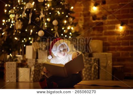 Little Boy Reading A Magic Book In Decorated Cozy Living Room. Portrait Of Happy Kid On Christmas Ev