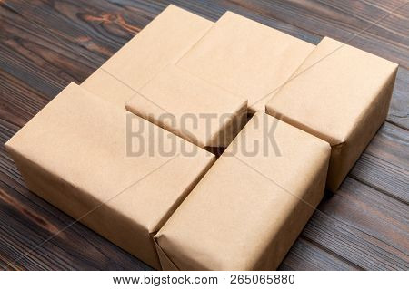 Brown Mail Package Parcel Blank For You Design. Cardboard Box On A Dark Wooden Background