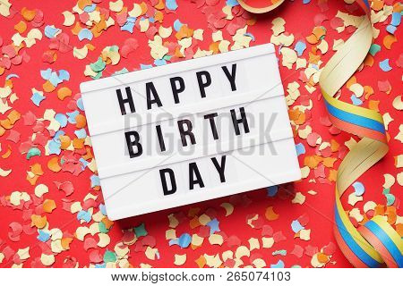Happy Birthday Greeting - Flat Lay Design With Confetti And Streamer - Text On Lightbox Sign On Red