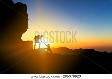 Teamwork Couple Helping Hand Trust Help Silhouette In Mountains, Sunset. Team Of Climbers Man And Wo