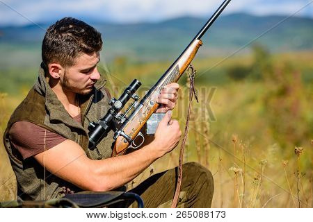 Hunting equipment concept. Hunter khaki clothes ready to hunt nature background. Hunting shooting trophy. Hunter with rifle looking for animal. Hunting hobby and leisure. Man charging hunting rifle poster