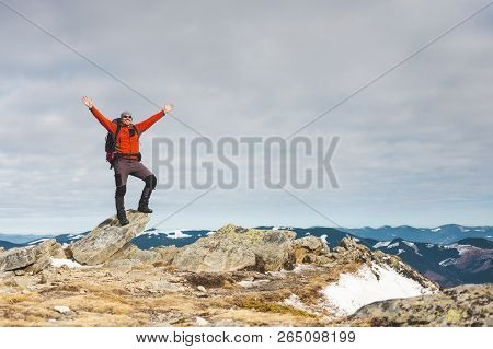 Climber With A Backpack On Top On A Sunny Day. A Man Went Up On The Mountain, People Traveling Throu