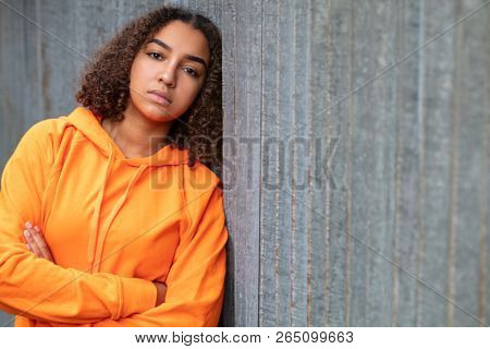 Beautiful mixed race African American girl teenager female young woman outside wearing an orange hoodie looking sad depressed or thoughtful