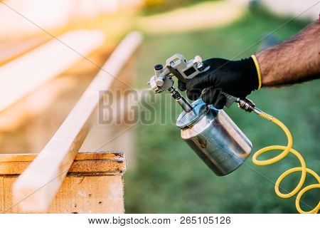 Industrial Handyman, Male Construction Worker Painting Wooden Blocks, Timber With Spray Gun On Site