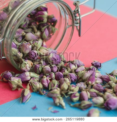 Square Photo Of Rose Bud Tea On Pink And Blue Background. Herbal Tea In A Jar, Selective Focus