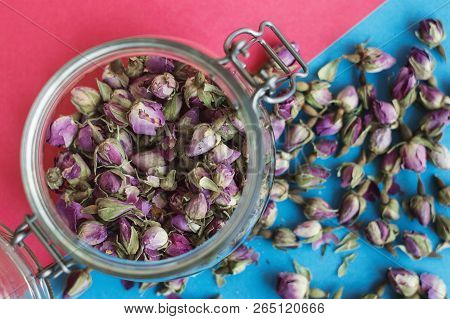 Dried Rose Buds In A Glass Jar On Pink And Blue Background, Top View. Herbal Tea