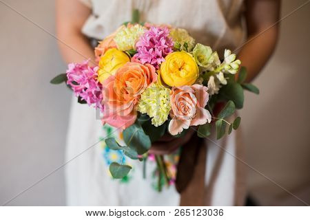Close Up Of Colorful Bouquet In Hands Of Florist In Floral Print Dress. Sunny And Fresh Mixed Flower