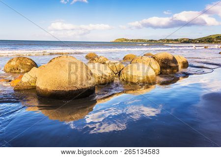 Boulders Moeraki - a group of large spherical boulders on the beach Koekokhe. Ocean evening tide. The concept of active, eco and photo tourism. Travel to New Zealand