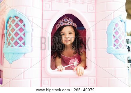 Cute girl wearing princess attire in playhouse at home poster