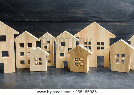 Wooden City And Houses. Concept Of Rising Prices For Housing Or Rent. Growing Demand For Housing And