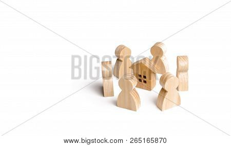 Wooden Figurines Of People Stand Around The House. Search For A New Home And Real Estate. Buying Or
