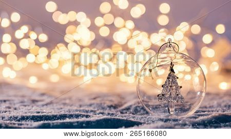 Christmas glass ball with tree in it on winter background. Snow and christmas lights.