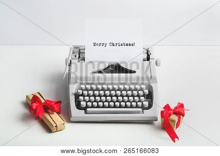 Vintage typewriter with MERRY CHRISTMAS text and gifts on white background. Wintertime holiday.