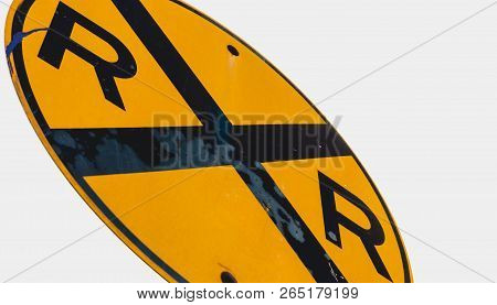 Abstract Dirty Dingy Railroad Crossing Sign Close Up With A White Sky