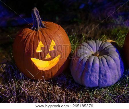 Pumpkin At Night Smiling At Friend On Hay Bail