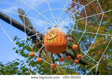 Spider Pumpkin Hanging From Cobweb With Fall Leaves In The Background