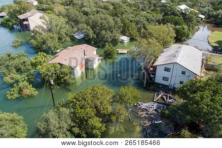 Aerial Drone View Of Historic Flooding In Central Texas , Three Flooded Houses With Water Almost Up