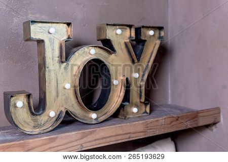 Wooden Letters Forming Word Joy Written On Grey Wall.christmas Postcard. The Inscription: Joy To The