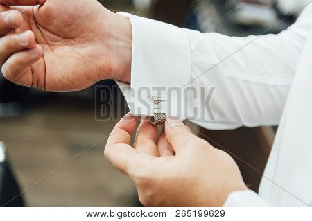Close-up of a man in a tux fixing his vintage cufflink. groom bow tie cufflinks poster