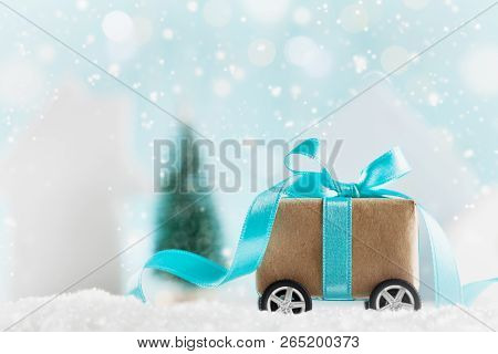Christmas Gift Or Present Box On Wheels Against Turquoise Bokeh Background. Holiday Greeting Card Wi
