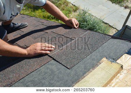 Roofer Installing Asphalt Shingles On House Construction Roof Corner. Roofing Construction. Roofing