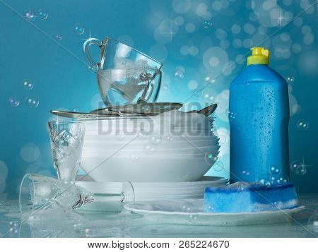 Clean Dishes And Cutlery On A Blue Background With Soap Bubbles