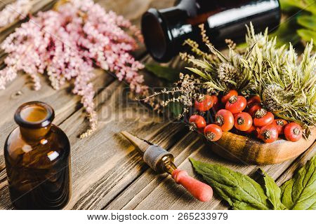 glass jars and flowers on wooden tabletop, alternative homeopathy medicine concept poster