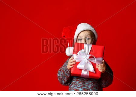 Funny Smiling Joyful  Child Boy In Santa Red Hat Holding Christmas Gift In Hand And Hide Behind The