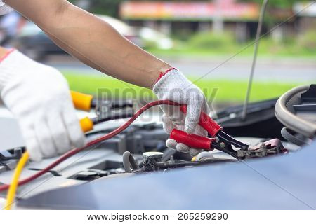 Car Mechanic Man Using Battery Jumper Cables To Charge A Dead Battery. Close Up Hand Charging Car Ba
