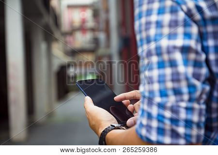 Man Holding, Touching Or Working On Mobile Phone With Blank Black Screen With Copy Space. Male Hands