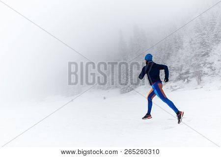 Woman Trail Running On Snow In Winter Mountains And Forest. Sport, Fitness Inspiration And Motivatio