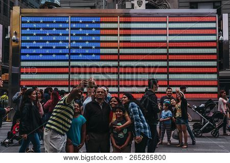 New York, Usa - May 28, 2018: Tourists Taking Selfies In From On A Big Led American Flag In Times Sq
