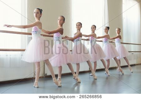 Young Girls Dancing Ballet In Studio. Group Of Young Ballerinas Training Choreography, Copy Space