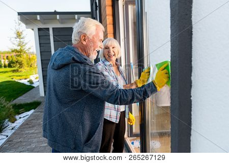 Modern Retired Couple Smiling Broadly While Cleaning Windows Outside Together