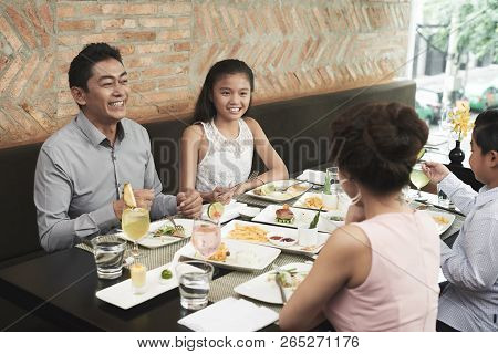 Happy Family Of Four Talking With Each Other During Lunch At Restaurant
