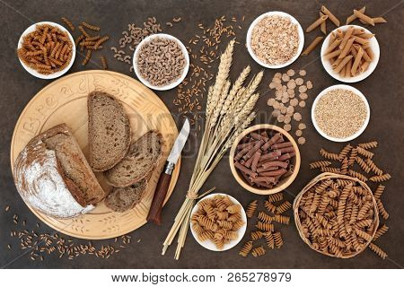 High fibre natural health food with whole wheat pasta, whole grain rye bread, oatmeal, oats, bran flakes and wheat sheath on lokta paper background.