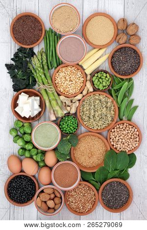 Health food high in protein with tofu, fresh vegetables, legumes, grains, dairy, supplement powders, seeds and nuts. Super foods high in dietary fibre, vitamins and antioxidants. Top view.