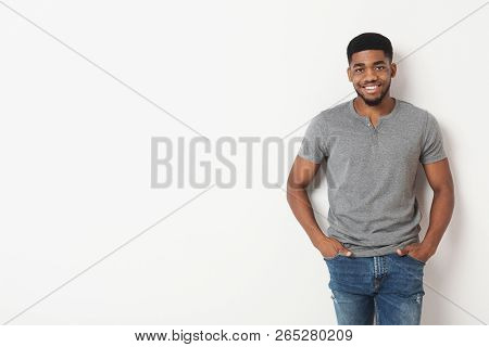 Young African-american Casual Man With His Hands In His Pockets, Smiling To Camera, White Studio Bac