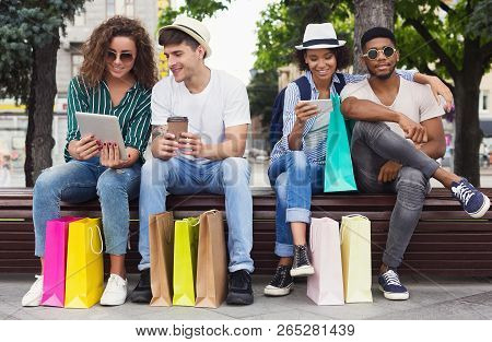 Gadget Addiction. Multiracial Women Using Gadgets While Sitting On Bench After Shopping