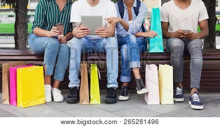 Gadget Addiction. Friends Using Gadgets While Sitting On Bench After Shopping