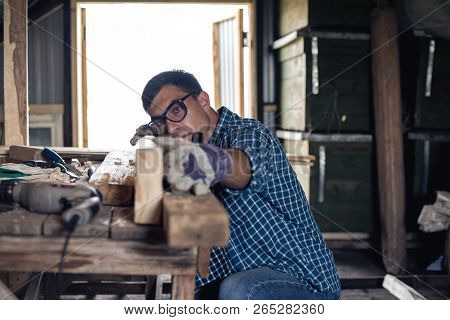 Joinery. The carpenter planes the wood in the workshop. Woodworking, roofing, diy poster