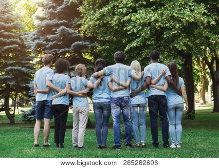 Volunteering, People And Ecology Concept. Group Of Volunteers Embracing In Park, Back View, Copy Spa